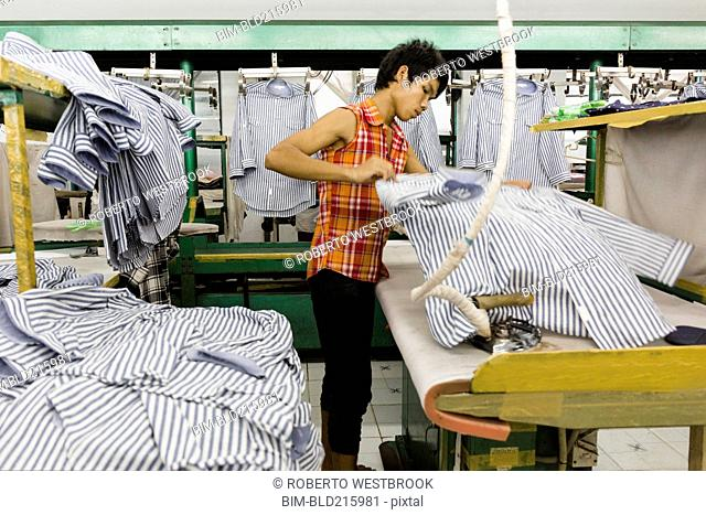 Asian worker ironing shirt in garment factory