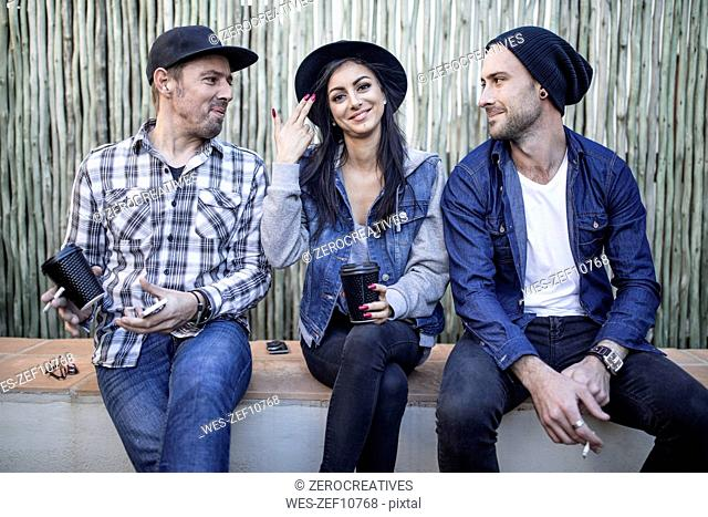 Portrait of young woman and two men sitting outdoors