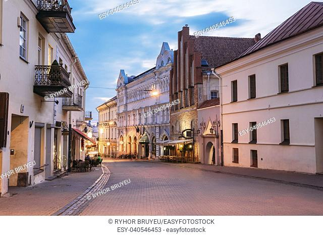Vilnius, Lithuania. View Of Illuminated Ausros Vartu Street, Famous Showplace Of Old Town With Outdoor Cafe And Ancient Red Brick Building In Summer Twilight...