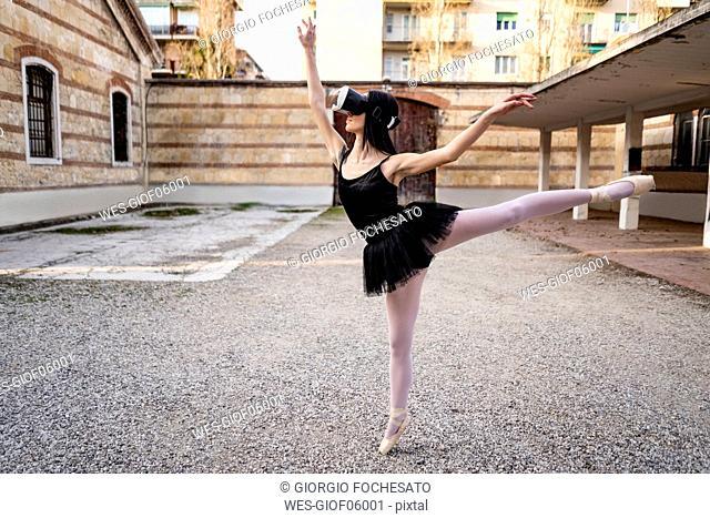 Italy, Verona, Ballerina dancing in the city wearing VR glasses