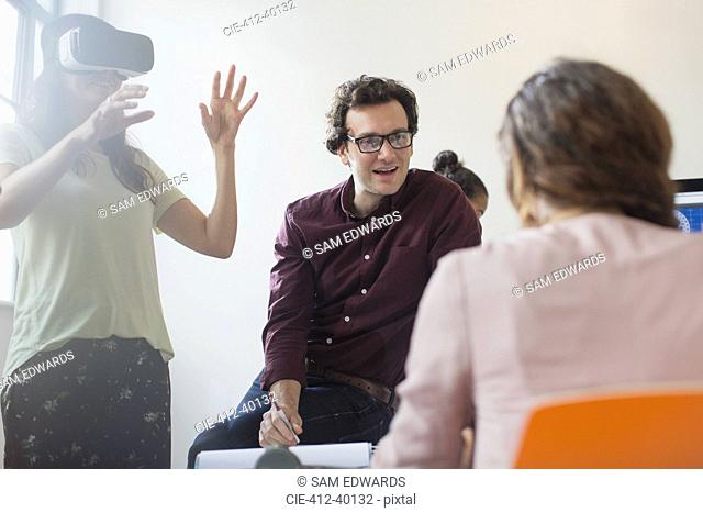 Computer programmers testing virtual reality simulator glasses in conference room meeting