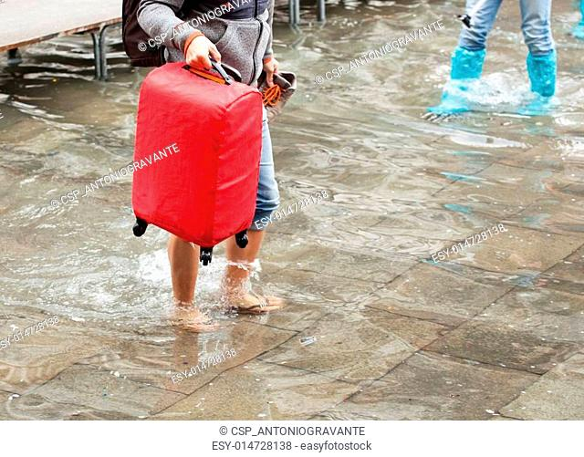 Asian tourist barefoot in the water with her luggage. Venice, It