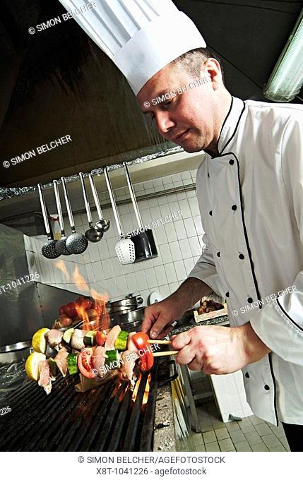 Chef Cooking Chicken Kababs in a Restaurant Kitchen