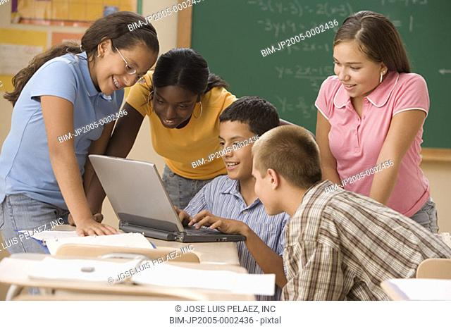 Students looking at laptop in classroom