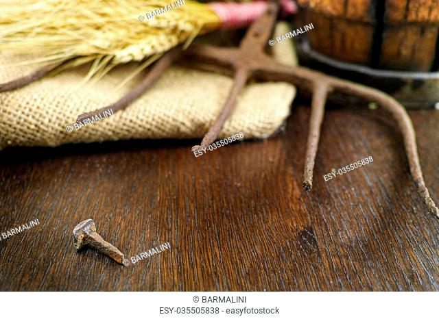 Antique pitchfork and forged nail on burlap sack against rural brick wall with whole wheat