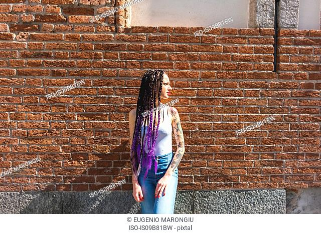 Woman standing next to red brickwall