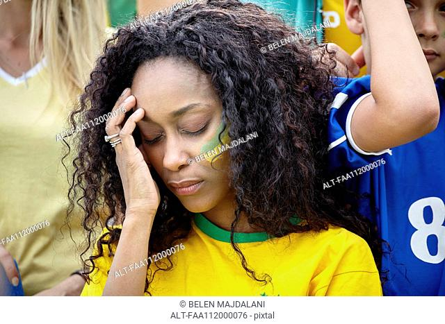 Woman holding head in disappointment at Brazilian football match