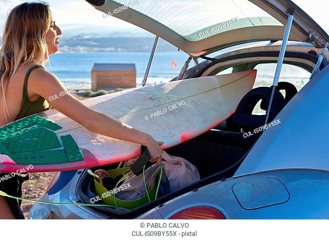 Young woman removing surfboard from car boot