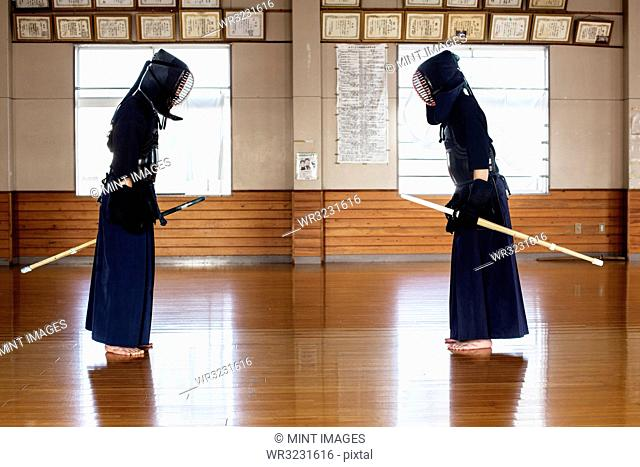 Japanese Kendo fighters standing opposite each other on wooden floor, bowing and greeting