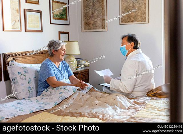 A doctor in a white coat and protective face mask making a home visit to a senior woman patient
