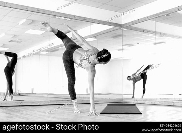 Fit sporty active girl in fashion sportswear doing yoga fitness exercise in in yoga studio. Active urban lifestyle. Black and white photo