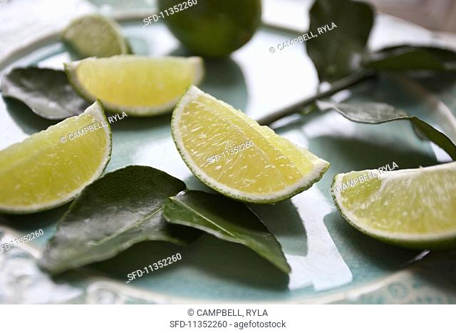 Lime wedges and keffir lime leaves on a plate