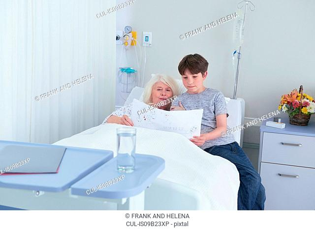 Senior female patient in hospital bed looking at grandson's drawing