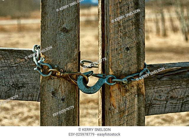 A close-up of a chain locking a wooden fence