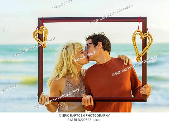 Caucasian couple holding frame with hearts and kissing