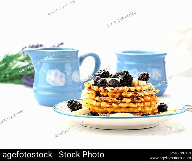 stack of baked Belgian waffles on a round plate with berries on a white table, delicious breakfast