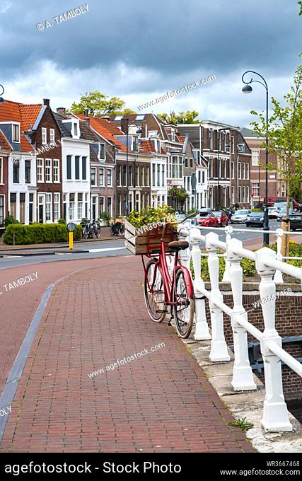 Netherlands, North Holland, Haarlem, Bicycle parked along railing of canal bridge with houses alongHooimarktstreet in background