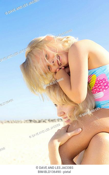 Caucasian mother carrying daughter on shoulders on beach