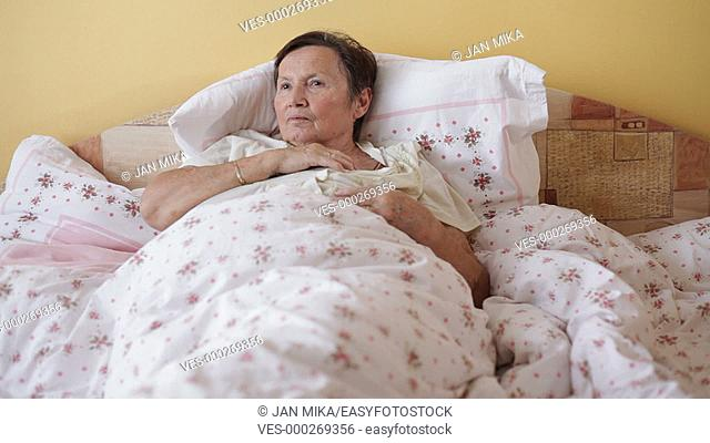 Sick senior woman checking temperature with thermometer in bed