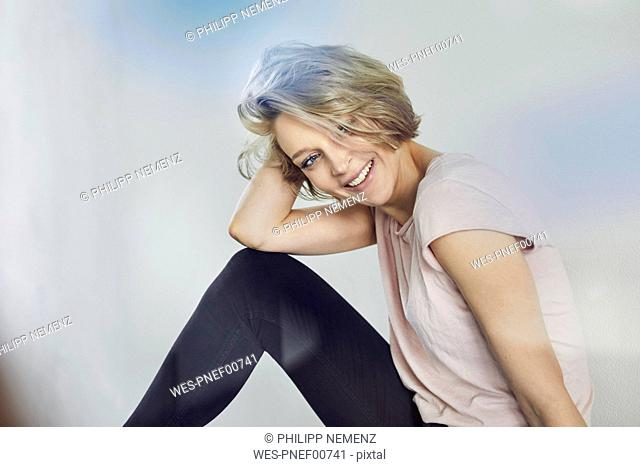 Portrait of happy blond woman sitting down