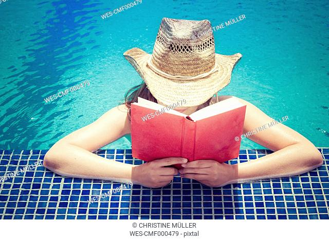 Woman wearing straw hat reading book at pool edge