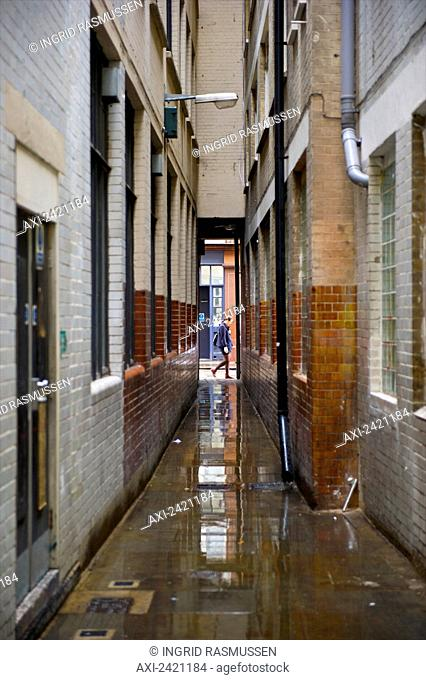 Water on the ground in an alleyway between buildings, Soho; London, England