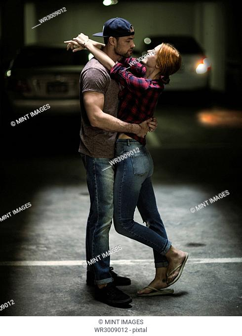 A couple dancing in an underground parking lot