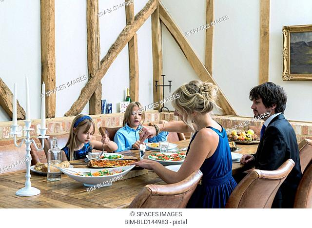 Caucasian family eating dinner in dining room