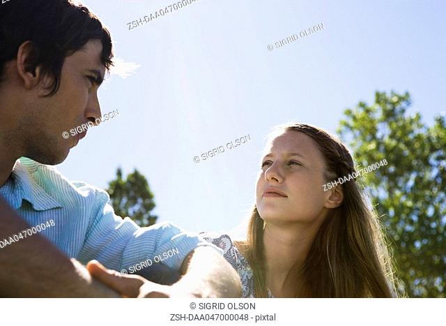 Young couple sitting outdoors, looking at each other