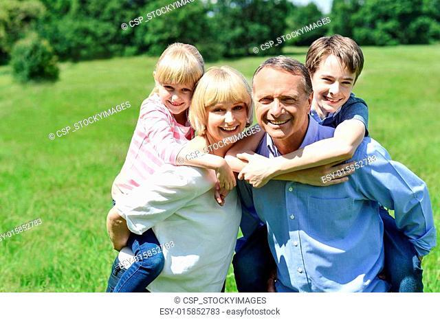 Kids enjoying piggy ride on parents back