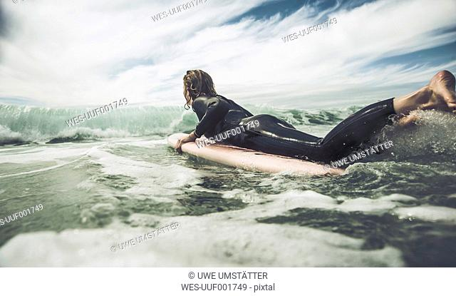 France, Bretagne, Camaret sur Mer, Teenage boy surfing at Atlantic coast
