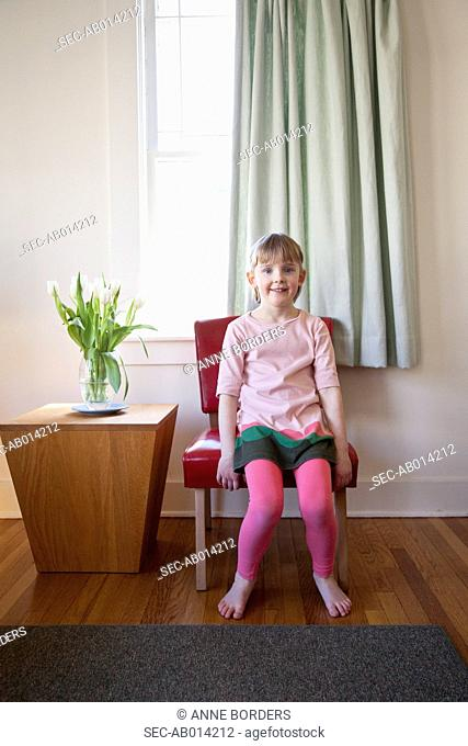 Smiling girl (4-5) posing on chair