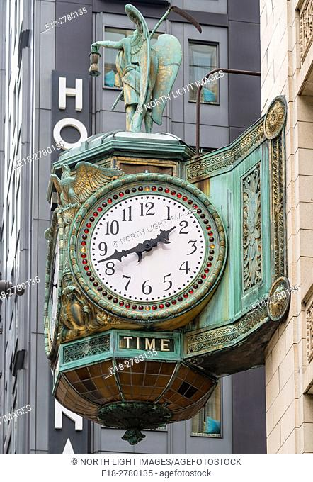 USA, IL, Chicago. Ornate clock on the side of art deco office building in downtown financial district