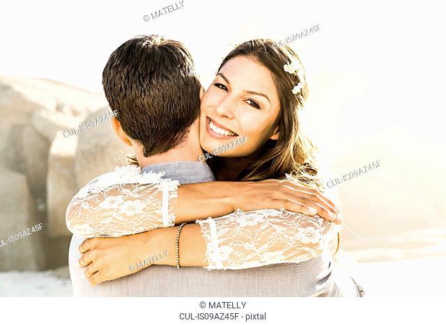 Portrait of woman hugging boyfriend on sunlit beach, Cape Town, South Africa