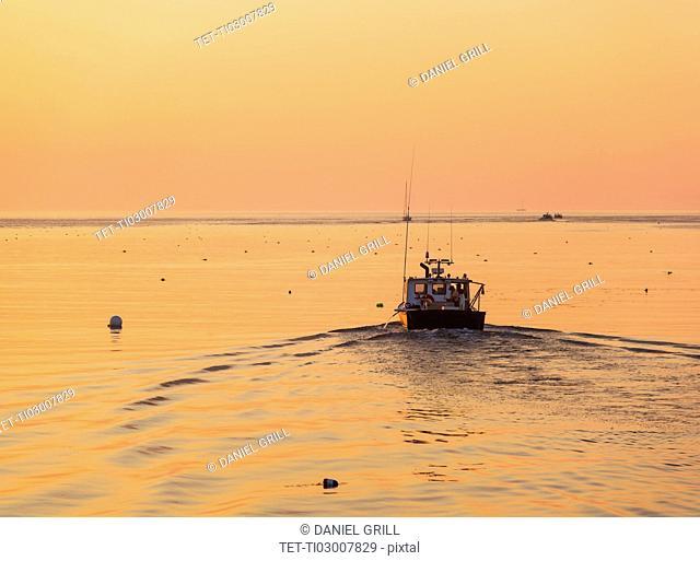 Boat on sea at sunrise