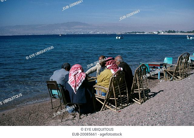 Group of men playing backgammon on shore of beach with Eliat and Israel in distance behind