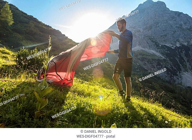 Austria, Tyrol, Hiker setting up his tent in the mountains