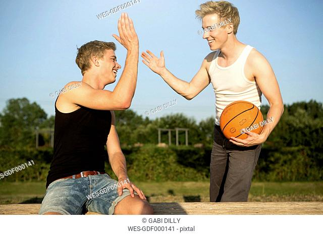 Germany, Two young men meeting up to play basketball