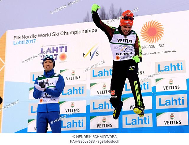 Johannes Rydzek from Germany celebrates his gold medal with a jump on the podium next to second placing Akito Watabe from Japan at the Nordic Ski World...