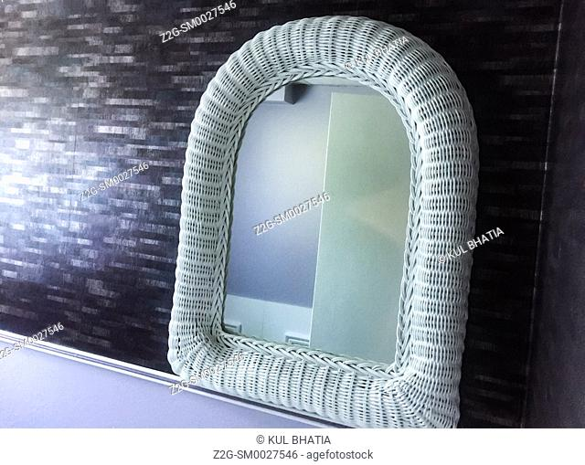 Stylish decor in pastel colours in a contemporary bathroom. White wicker frame lends an oriental touch