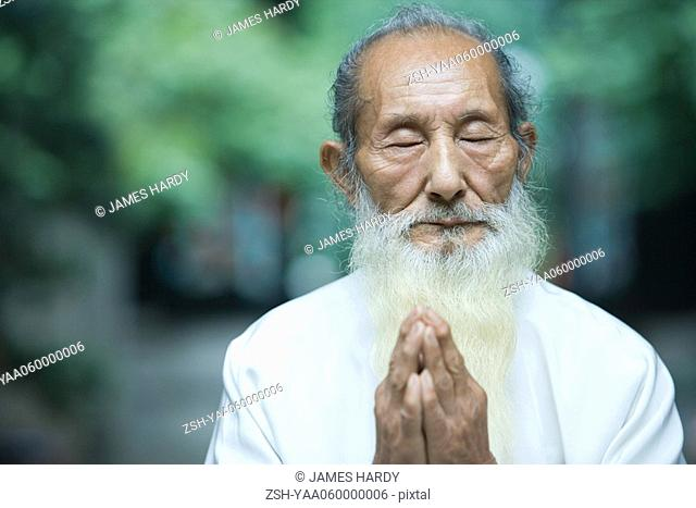 Elderly man in traditional Chinese clothing, hands clasped in prayer