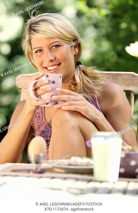 portrait of woman having breakfast in garden drinking coffee