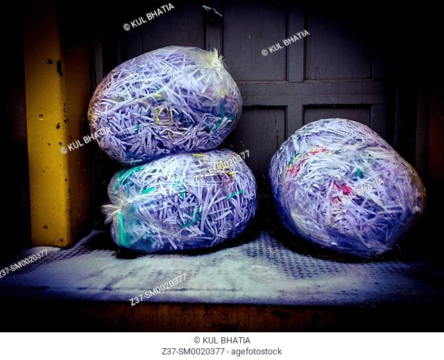 Three bags of shredded documents await pick up at the loading dock of a building, Ontario, Canada