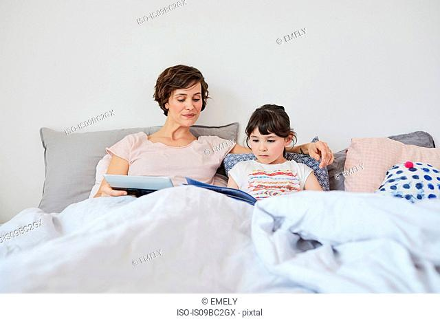 Mother and daughter relaxing in bed, daughter reading book, mother holding digital tablet
