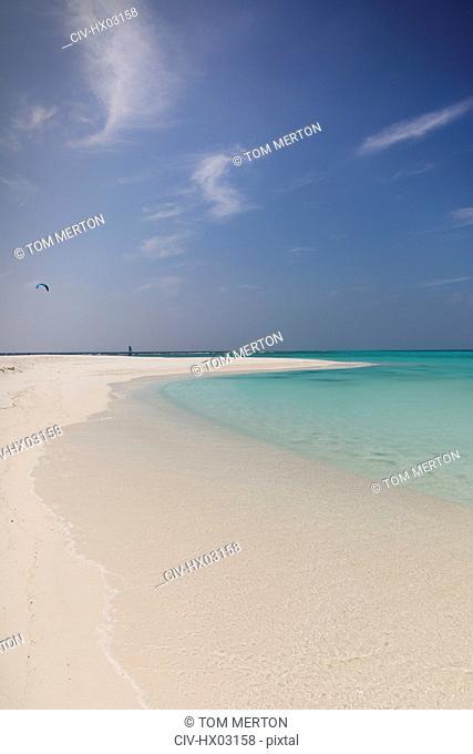 Tranquil tropical ocean beach under sunny blue sky