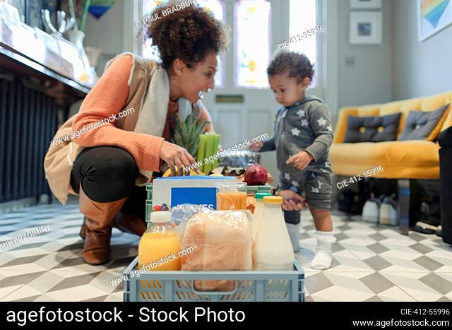 Mother and baby daughter receiving grocery delivery in foyer
