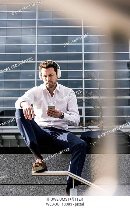 Businessman sitting in front of office building, wearing headphones