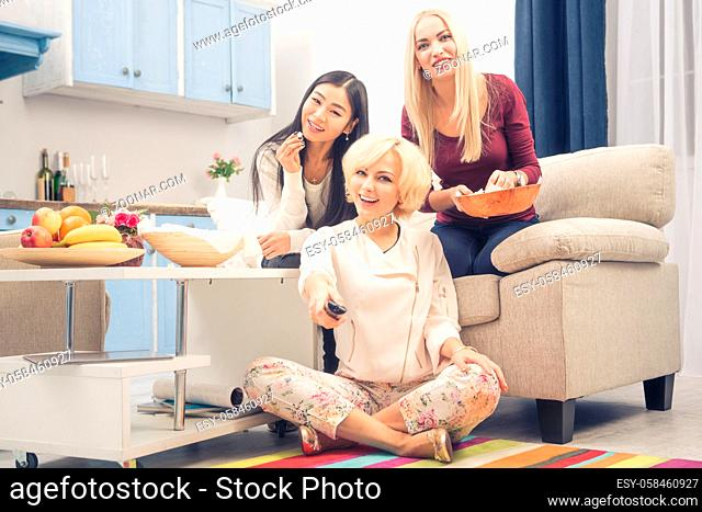 Toned picture of best friends girls watching interesting films or movies on television while having party in kitchen at home