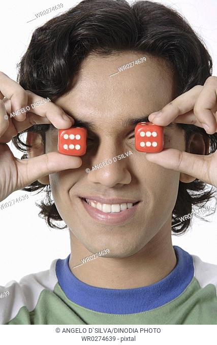 Teenage boy holding two red coloured dices in front of face MR 687T