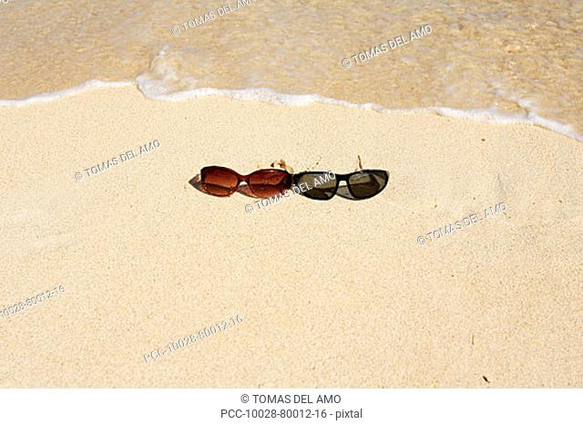 Sunglasses in sand on beach, foaming shore waters